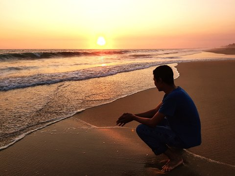 Side View Of Man Crouching On Beach Against Sky During Sunset