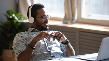 Distracted from job study happy millennial african american man in glasses listening to favorite...