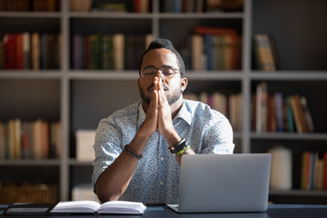 Fototapeta Front view frustrated millennial african american guy sitting at able with computer, praying god with folded hands, asking good luck before business start. Hopeful young biracial man making decision. obraz