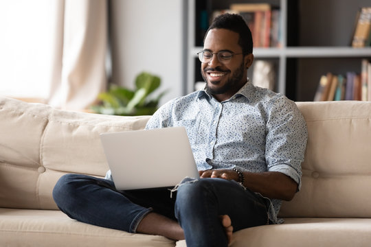 Smiling young african american man in eyewear relaxing on couch, looking at laptop screen. Happy multiracial guy web surfing internet, chatting with friends in social network, watching movie at home.