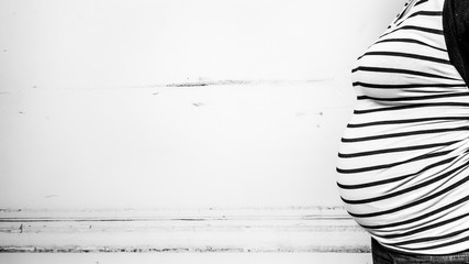Fototapeta Midsection Of Pregnant Woman Standing Against Wall