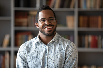 Happy young african american businessman entrepreneur in glasses, head shot portrait. Smiling millennial biracial man in eyewear looking at camera, posing for photo in modern office, library or home. Fotomurales