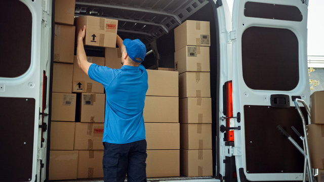 Courier Takes out Cardboard Box Package from Delivery Van Full of Parcels, Delivering Postal Parcel.
