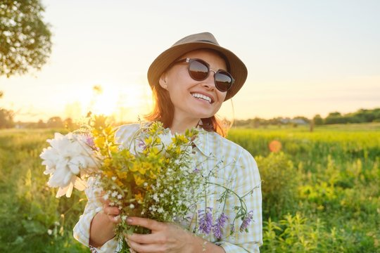 Outdoor portrait of mature happy smiling woman with spring flowers