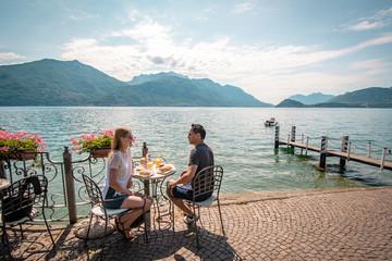Junges Paar frühstückt direkt am Comer See in Italien  Wall mural