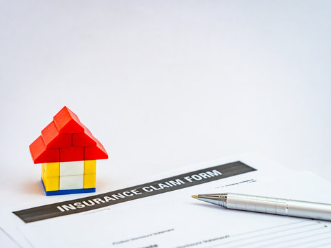 A lego house toy with insurance claim form and a ball pen shot on white background with copy space.