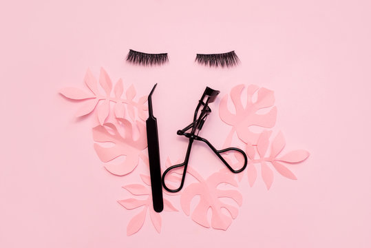 Black false lashes strips and tweezers on pink background with paper palm leaves