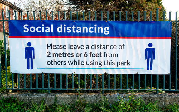 Large banner attached to railings, warning the general public to keep to the social distancing rules whilst using the public parks, in the London Borough of Bexley.