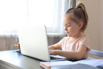Distance learning. Cheerful little girl using laptop computer studying through online e-learning system.