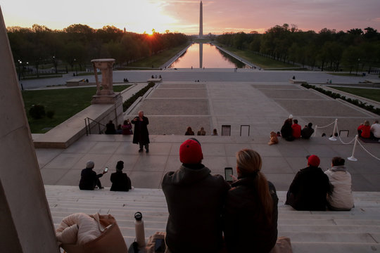 People sing an Easter hymn on the steps during sunrise at the Lincoln Memorial during the coronavirus disease (COVID-19) outbreak in Washington
