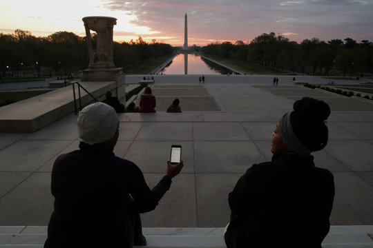 Women sing an Easter hymn on the steps during sunrise at the Lincoln Memorial during the coronavirus disease (COVID-19) outbreak in Washington