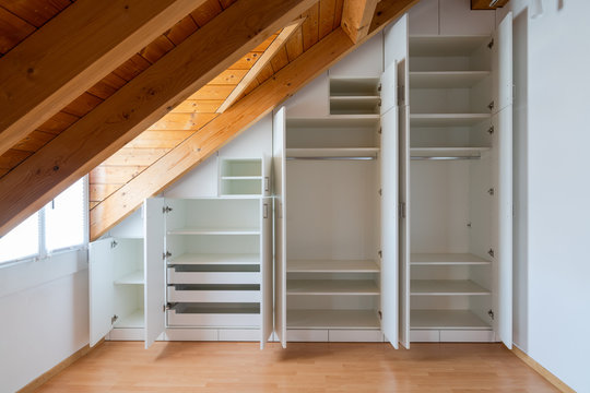 interior view of a custom-made closet with open doors built into a master bedroom with a sloping roof