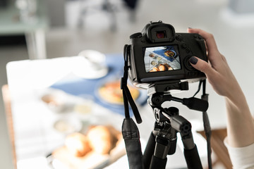 Photographer taking pictures of food. Photo camera on a tripod