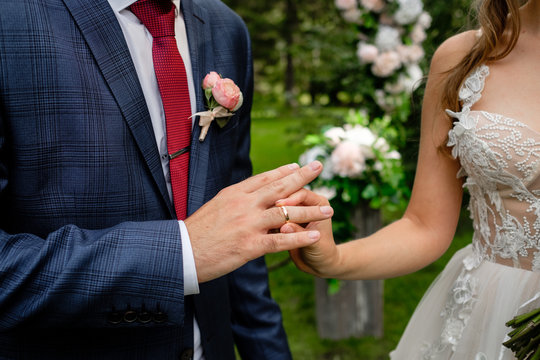 The bride puts the ring on the finger of groom