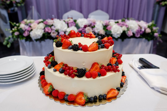 A large wedding cake decorated with strawberries. In the background is wedding decor