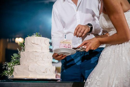 Wedding day. Bride and groom cut big white cake