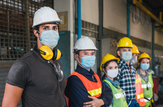 Group of diverse team of workers wearing face mask and protective helmets standing in front of the factory