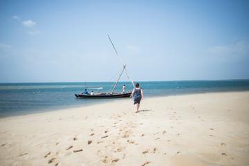 Woman walking towards traditional sailboat on sand beach Wall mural