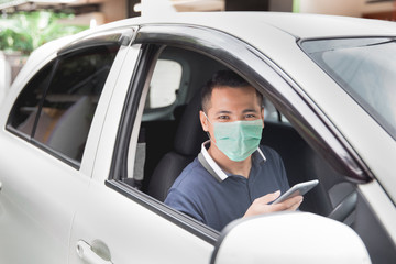 young handsome male using mobile phone while driving his car Wall mural