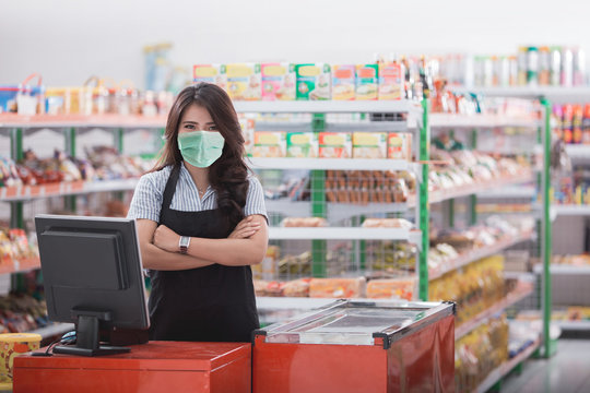 Portrait of smiling asian female cashier staff standing at cash counter in supermarket