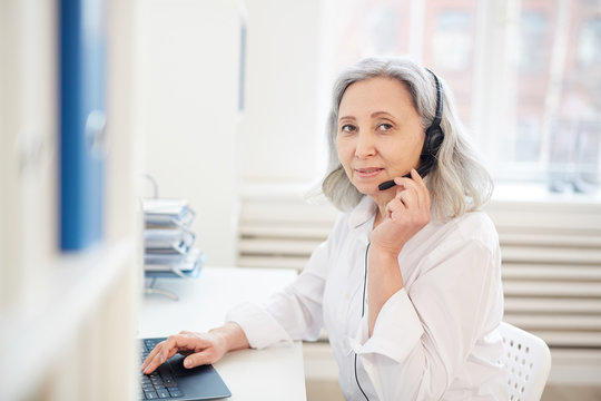 Waist up portrait of senior businesswoman speaking to microphone and looking at camera while working with laptop in office interior, copy space