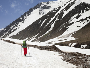 Fototapete - Hiker with big hiking backpack walking on snow covered glacier in high mountains