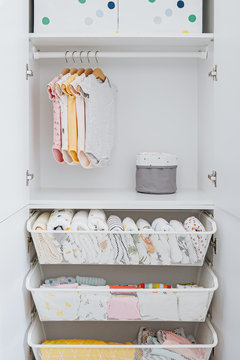 Set of baby bodysuits for a newborn girl and boy on hangers in white wardrobe. Motherhood, cleaning home kids wardrobe. Minimal fashion concept.