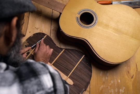 Luthier's workshop table. craftsman debating wood with gouge. dark black background.