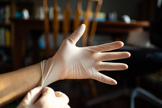 wearing disposable latex gloves to avoid the contact with viruses on the frequently touched surfaces