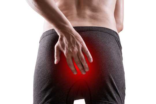 Man suffering from hemorrhoids, anal pain, isolated on white background