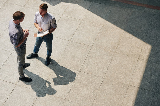 Young businessman with opened planner standing outdoors and talking to colleague about work, view from above