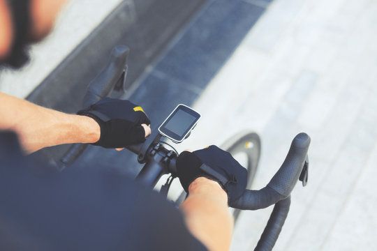 Close up Of Road Bike With GPS Navigator With Smart Watches on Cycle Handle Bar. Athletic Cyclist Man Riding Sport Bike At City