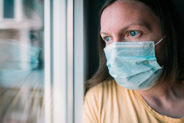 Woman in self-isolation during virus outbreak looking through window