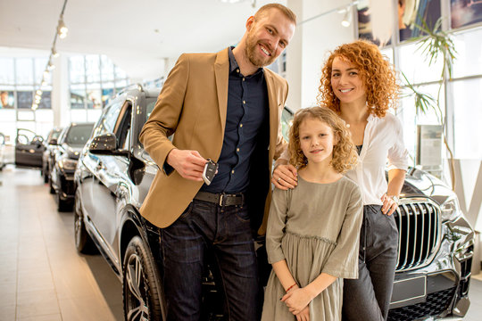 happy caucasian family came to get new automobile in dealership. cheerful people are future owners of perfect car, they make purchase in cars shop