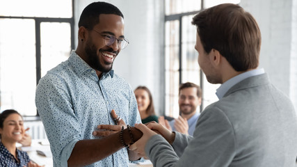 Caucasian businessman handshake African American male employee congratulate with work achievement or success, boss shake hand of biracial worker greeting with job promotion at office meeting