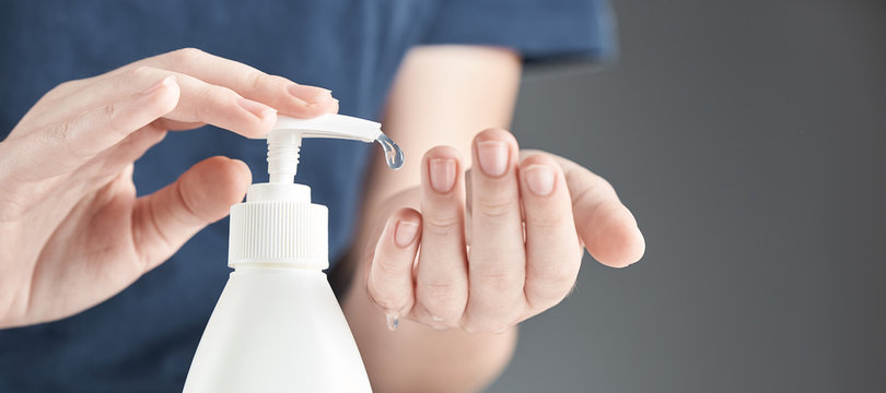 Female hands using hand sanitizer gel pump dispenser on a gray background.