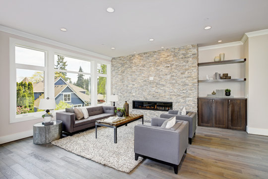 Modern great room with a floor to ceiling stone fireplace. Luxury American modern home.