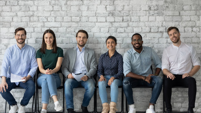 Portrait of smiling diverse multiracial young people sit in row on chairs wait for office interview, happy motivated multiethnic job candidates hired for vacant work position, employment concept