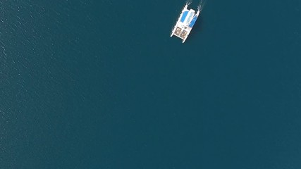 Wall Mural - Lone sailboat on the sea surface. Aerial top view