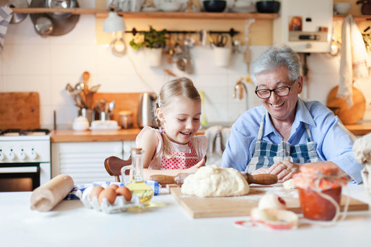 Family cooking at home. Grandmother and child have fun. Making italian food and meal in cozy kitchen. Senior woman and little girl baking. Cute kid is helping to prepare dinner. Children chef concept.