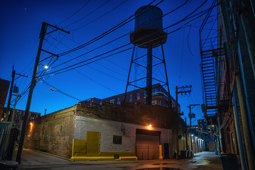 Fototapete - Industrial urban street city night alley scenery in Chicago with a vintage warehouse, factory and a water tower after a rain.