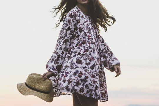 Midsection of woman in floral sundress standing outdoors