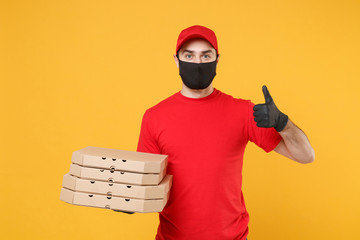 Delivery man employee in red cap t-shirt uniform black mask gloves give food order pizza boxes isolated on yellow background studio. Service quarantine pandemic coronavirus virus flu 2019-ncov concept