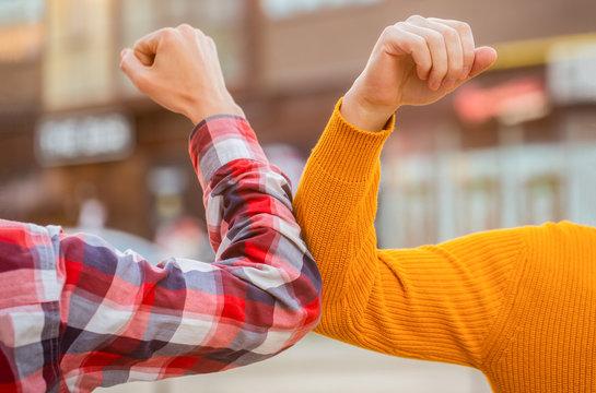 Elbow bump. Bump elbows. Friends shaking elbows outdoors. Elbow greeting style. Coronavirus epidemic. Coronavirus, illness, infection, quarantine, COVID-19. Don't shake hands. Stop handshakes