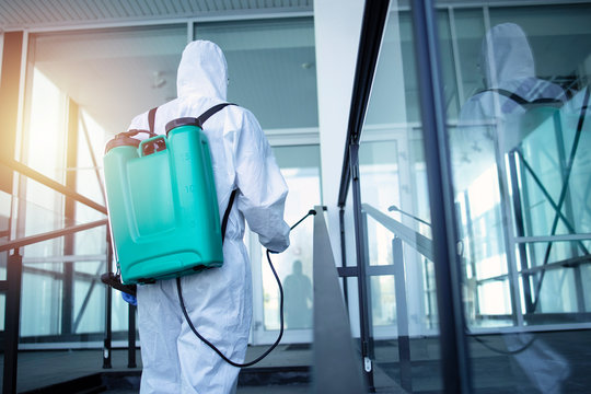 Unrecognizable person in white protection suit disinfecting public areas to stop spreading highly contagious coronavirus. Man with tank reservoir on his back spraying disinfectant to kill COVID-19.