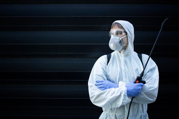 Portrait of professional exterminator holding sprayer with chemicals for pest control. Copy space provided.