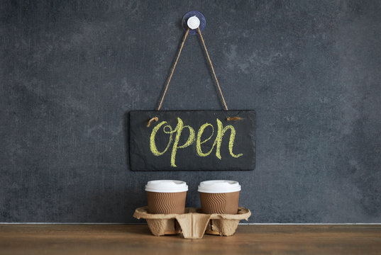 A sign that says Open on cafe, on a black chalk board. After quarantine. Takeaway coffee glasses on dark background. Business opening