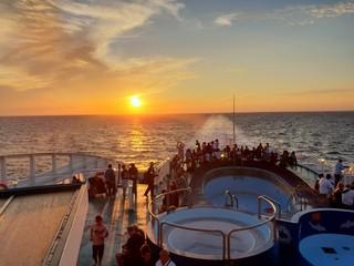 Fototapeta People In Boat On Sea Against Sky During Sunset