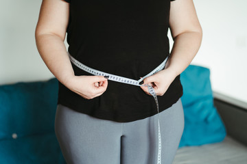 weight loss, overweight, plus size, diet. fat woman measures her waist with measuring tape Papier Peint