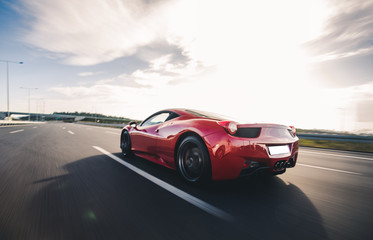 Red luxury model sport car view from behind on the highway Wall mural